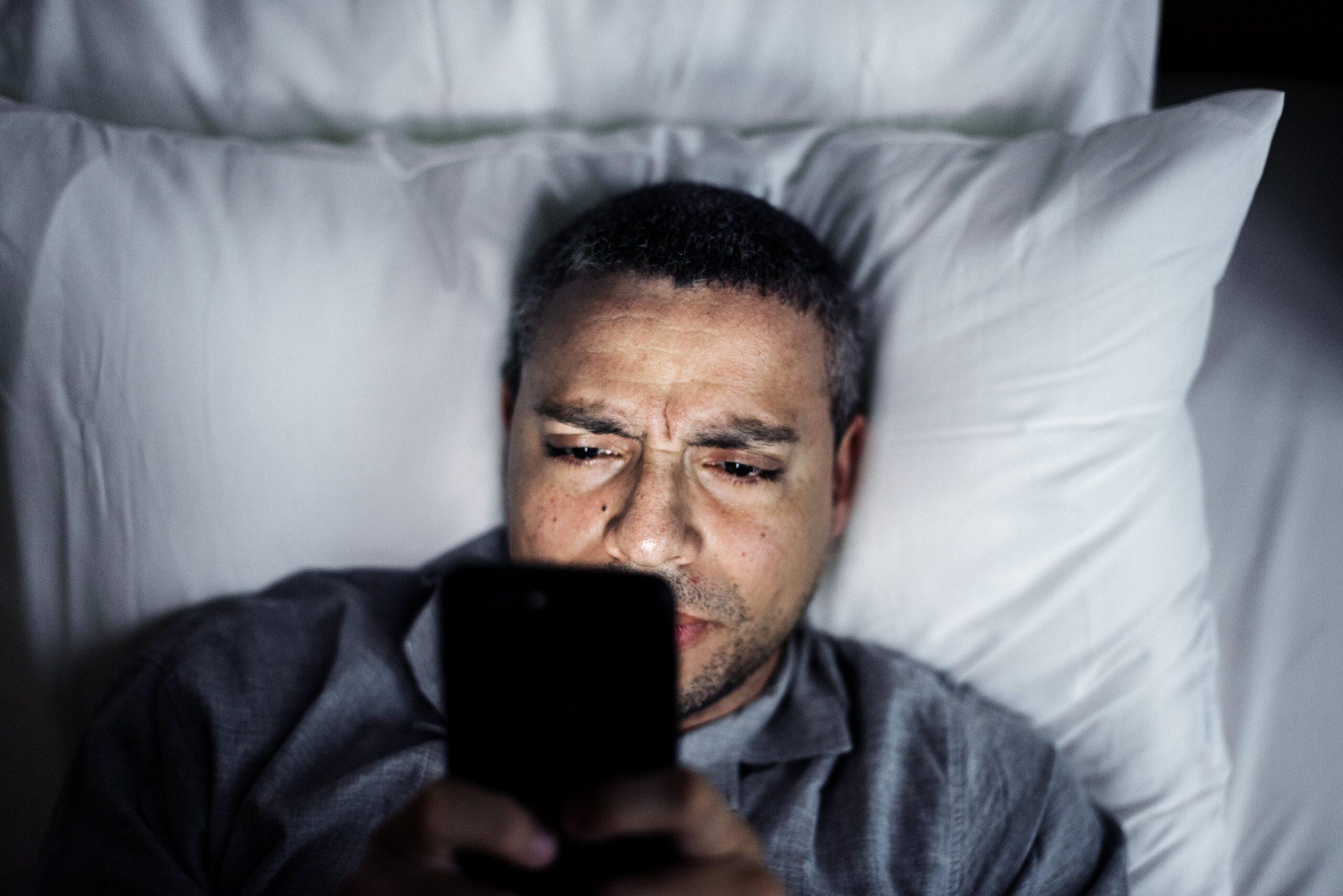 Uomo che usa lo smartphone nel letto